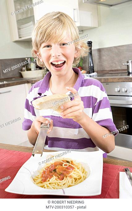 Portrait of a happy boy grating cheese over spaghetti, Bavaria, Germany