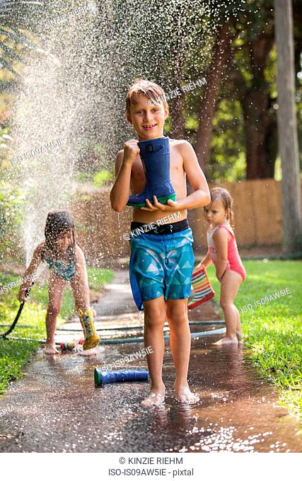 Boy carrying welly on sidewalk, girls playing with water hose in background