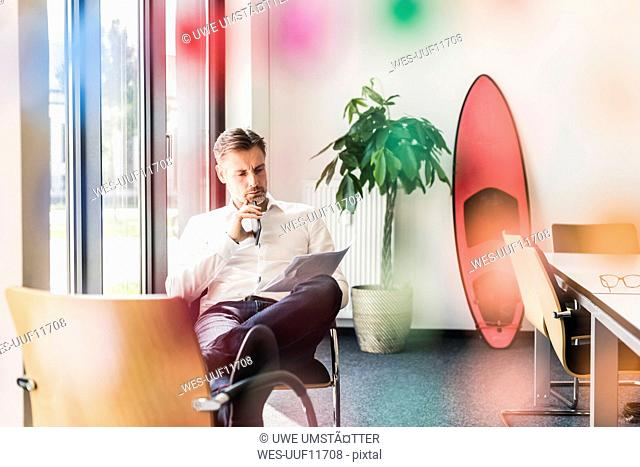 Businessman looking at documents with surfboard leaning against wall