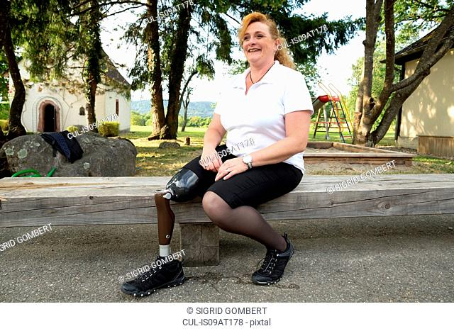 Mid adult woman with prosthetic leg, sitting on fence