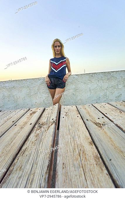 model woman leaning against wall behind wooden table during sunset. Australian ethnicity. During holiday stay in Hersonissos, Crete, Greece