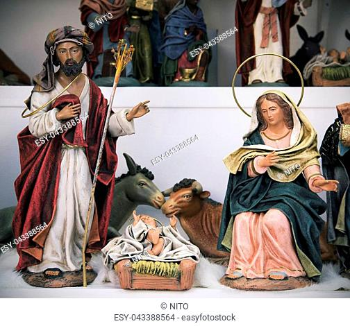 some classical figurines depicting the Holy Family, the Child Jesus, the Virgin Mary and Saint Joseph, and the donkey and the ox on sale in a Christmas market
