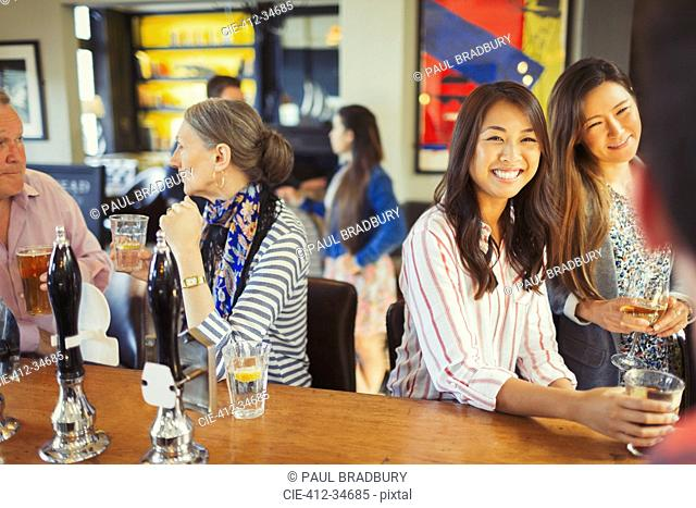 Women smiling at bartender and drinking at bar