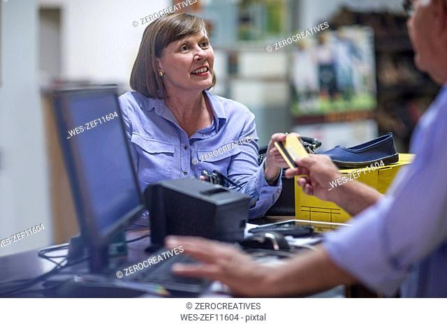 Woman buying shoes paying with credit card
