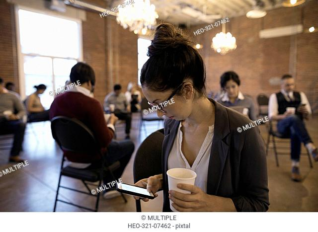 Businesswoman drinking coffee texting with cell phone on conference coffee break