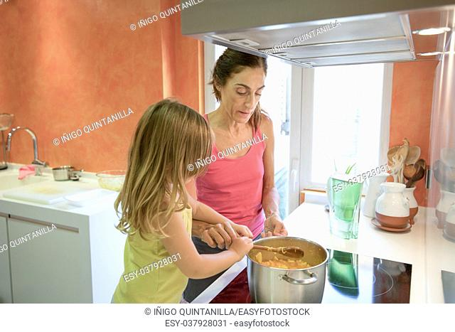 Woman mother and four years old blonde child in the kitchen cooking together as a team, in electrical cooktop with a saucepan