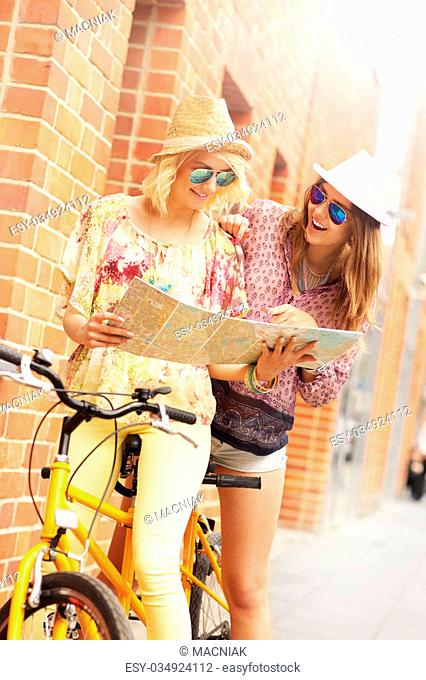 A picture of two girl friends using a map and riding a tandem bicycle in the city