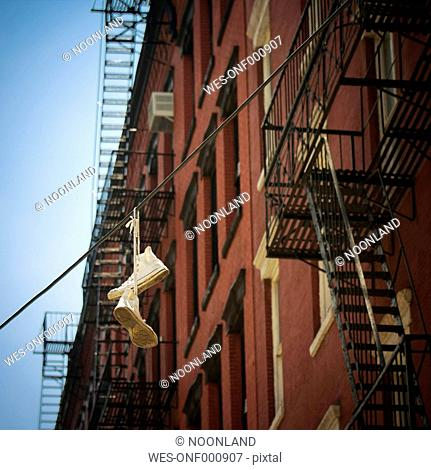 USA, New York City, SoHo, Trainers hanging on electric cable