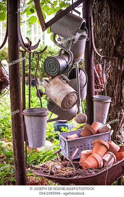 A garden vignette collection of watering cans, tools, buckets and terra cotta pots.Georgia USA