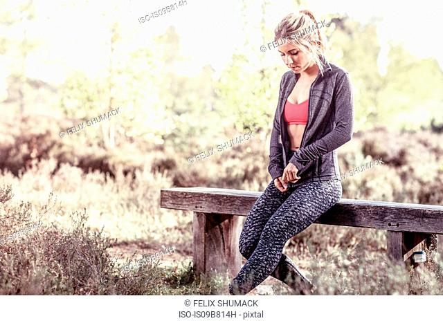 Young woman in rural setting, sitting on bench, zipping up sweatshirt