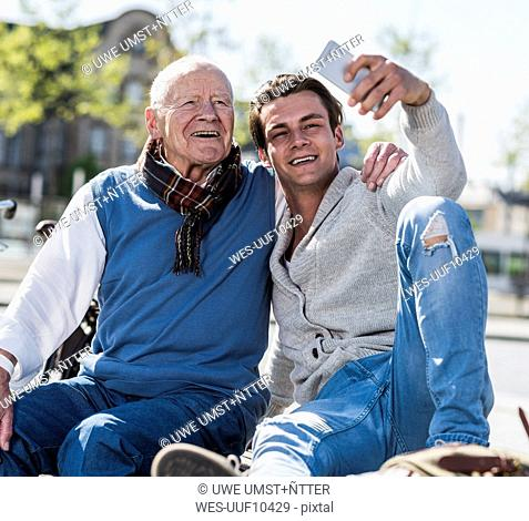 Senior man and adult grandson on a bench taking a selfie