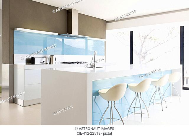 White and clean modern kitchen with stools at kitchen island