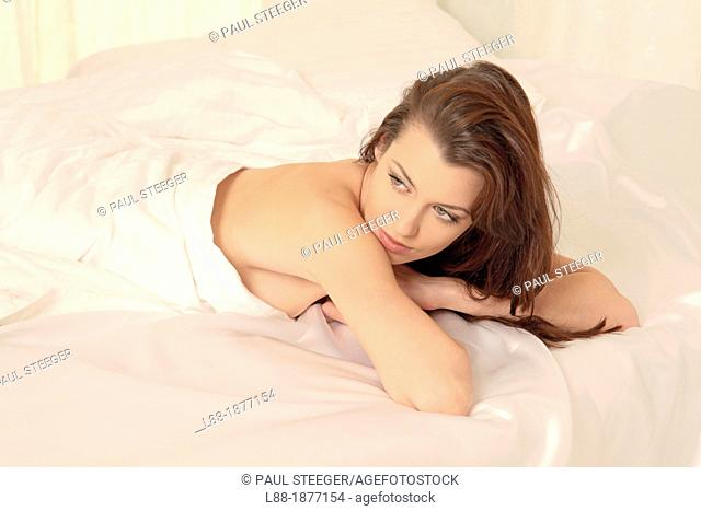 Germany, Young woman lying in bed