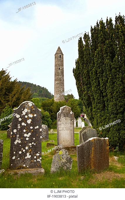 gravestones in a cemetery and a round tower on a 6th century monastic site, glendalough, county wicklow, ireland