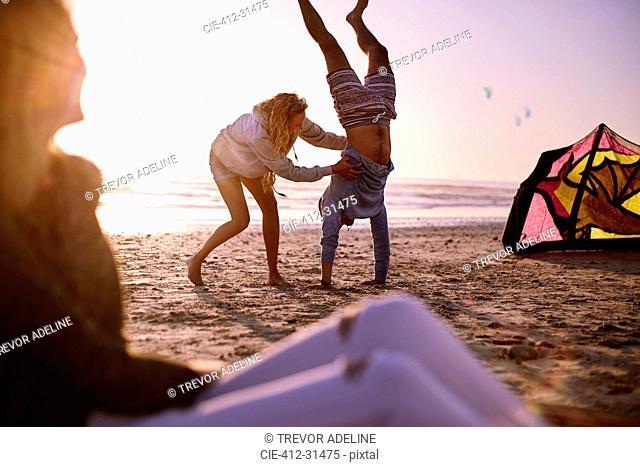 Woman holding man doing handstand on sunset beach