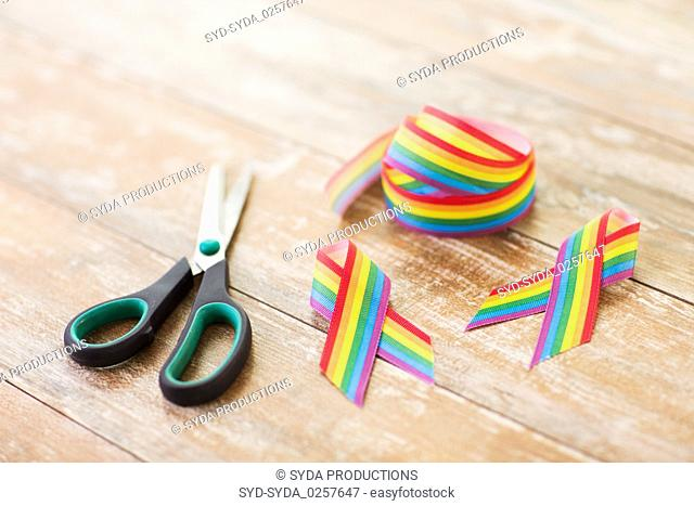 gay awareness ribbon and scissors on wooden boards