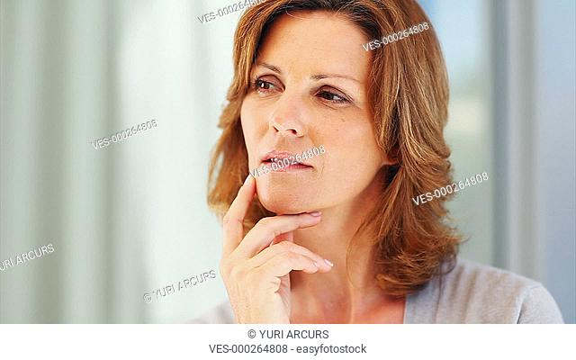 Pretty mature woman looking very thoughtful