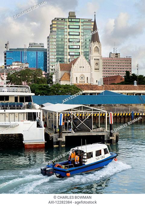 A boat in the harbour and a view of St. Joseph's Cathedral; Dar es Salaam, Tanzania