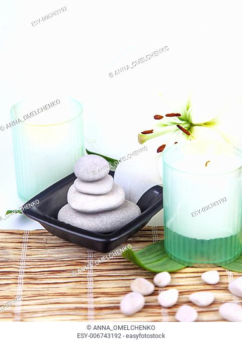 Photo of spa stones and candles decorated with white lily flower, beautiful still life on table in spa salon, essential oil for massage, zen balance