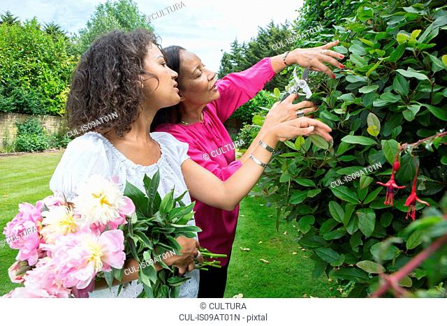 Mother and grown daughter in garden together