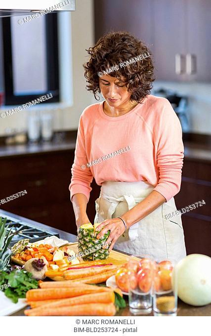 Hispanic woman slicing pineapple