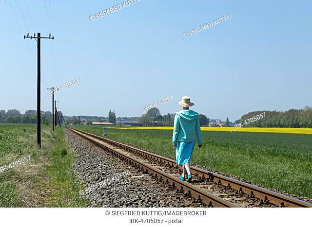 Woman running on railway tracks, Klein Bollhagen, Mecklenburg-Western Pomerania, Germany