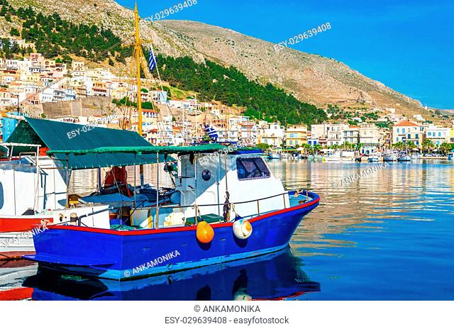 Blue wooden boat in peaceful port with clear blue sky