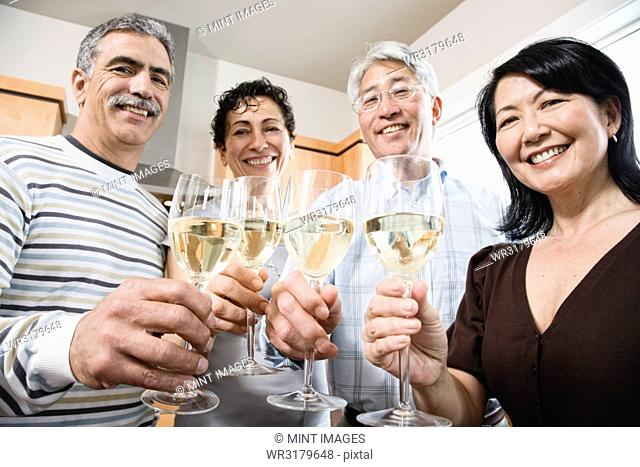 Two couples in a kitchen, Asian and Caucasian men and women making a toast with glasses of white wine