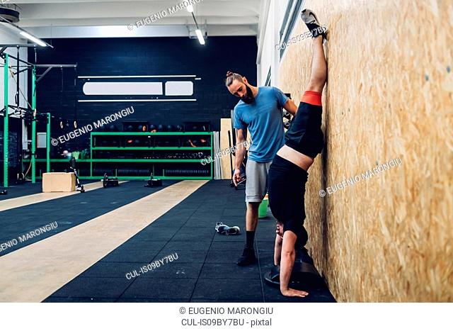 Man with disability doing handstand against chipboard wall