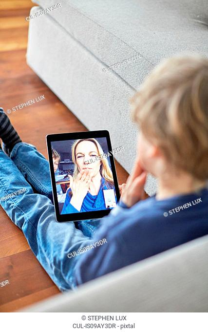 Boy sitting on floor blowing a kiss to mother on digital tablet video call