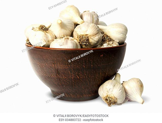 Whole head of garlic in ceramic bowl isolated on white background
