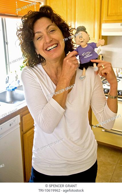 A 50-year-old woman smiles happily while holding a Fifty and Fantastic doll joke gift at her birthday party in Mission Viejo, California
