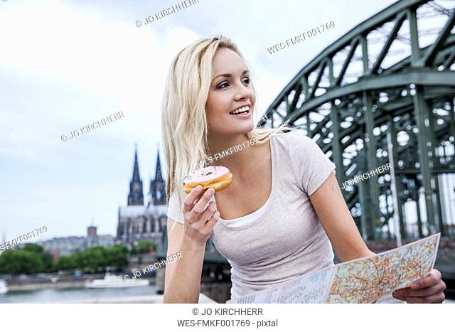 Germany, Cologne, portrait of young woman with bagel and city map