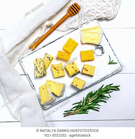 small pieces of brie cheese, roquefort, camembert, cheddar and cheese with walnuts on a white wooden board,