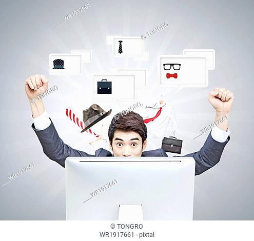 a business man cheering next to screen