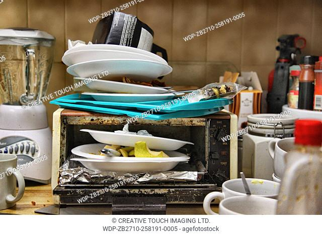 Styrofoam plates with old food piled in and on a toaster oven on a messy kitchen countertop