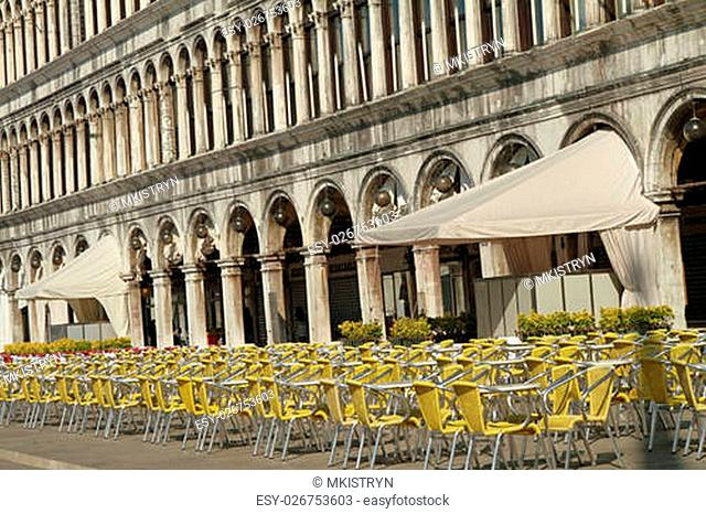 Many empty tables and chairs on the early morning on Piazza San Marco with buildings of the Procuratie Vecchie, place of old