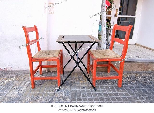 Two red wood and straw chairs and simple table outside small restaurant in Palma de Mallorca, Balearic islands, Spain