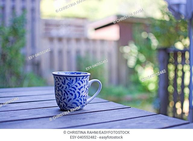 Mug in blue pattern on wooden table outdoors in the shade in a garden