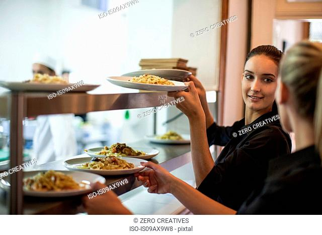 Waitress taking meal off kitchen counter for customer