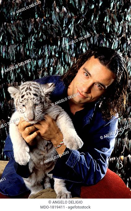 Italian singer-songwriter Eros Ramazzotti posing with a tiger cub while shooting the music video of the song Ancora Vita. Italy, 1991