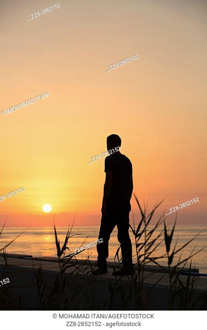 Full length silhouette of a male figure walking on the beach at sunset