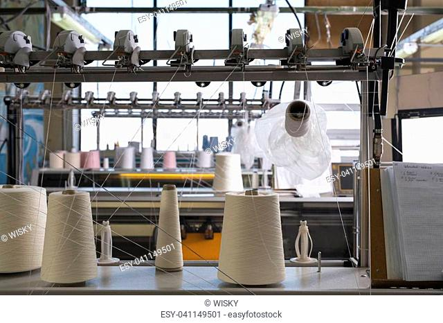 Big spools with white thread at rewinding machine view
