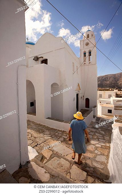 Elderly local woman walking down the stairs in Artemonas village, Sifnos, Cyclades Islands, Greek Islands, Greece, Europe