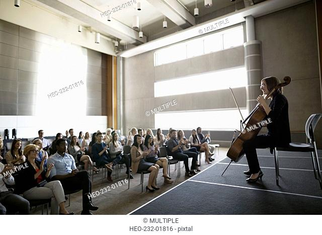 Audience watching female cellist perform on auditorium stage