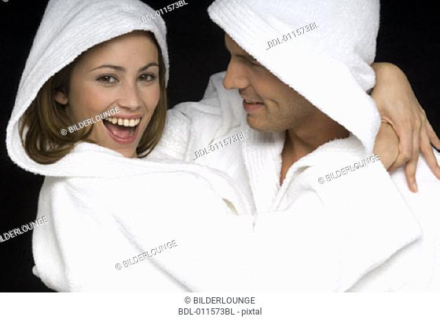 young couple playing around in bathrobes