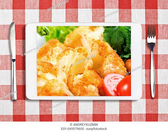 white tablet pc with dish, fork and knife on red checked tablecloth
