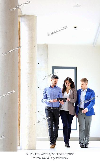 Three executives looking at tablet
