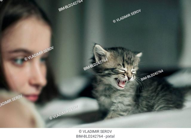 Caucasian woman watching yawning kitten