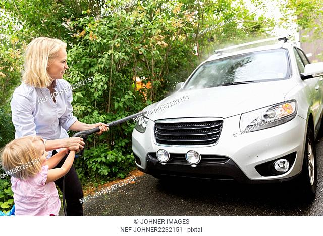 Woman with daughter cleaning car